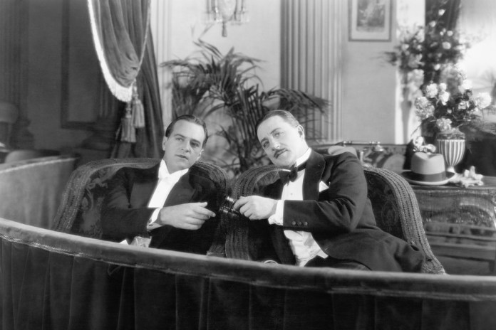 black-and-white photograph of two white men sharing opera glasses ina theater box