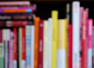blurred photograph of bookshelf with birght, colorful books