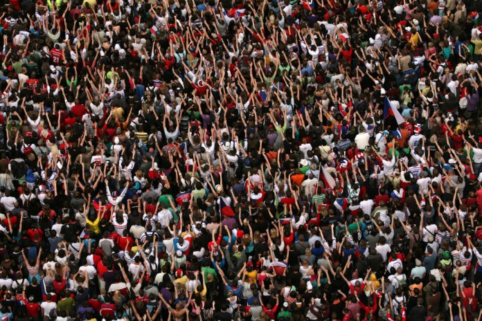 photograph of huge crowd from above, many with arms raised
