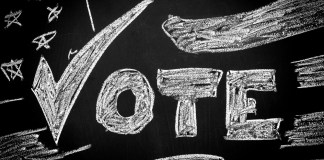 "photograph of ""Vote"" written on chalkboard with drawing of American flag"