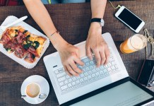 overhead photograph of hands on laptop on dinner table surrounded by food and beverages