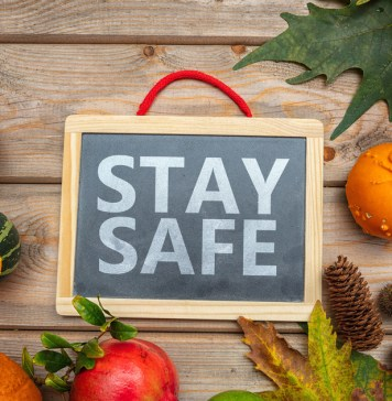 "photograph of ""Stay Safe"" message among pumpkins and thanksgiving background"