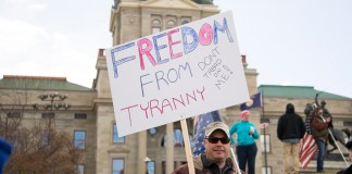 "photograph of protester holding sign reading: ""Freedom from Tyranny Don't Tread on Me"" in front of State building"