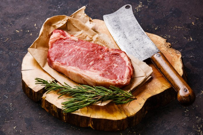 photograph of raw steak arranged on butcher block with cleaver and greenery
