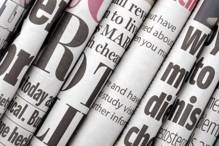 photograph of partial newspaper headlines arranged in a stack