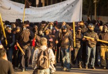 photograph of threatening protestor group with gas masks