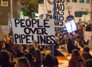 "photograph of protestors with ""People over Pipelines"" sign"