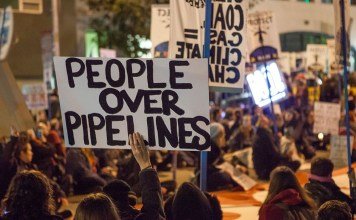 """photograph of protestors with """"People over Pipelines"""" sign"""