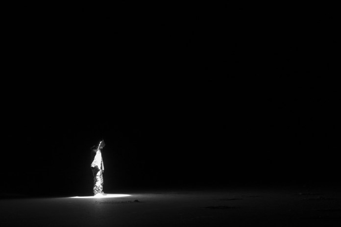 photograph of single person with flashlight standing in pitch darkness