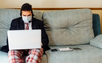 photograph of masked businessmen in tie and pajamas working at laptop at home