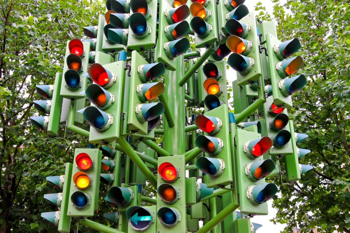 photograph of a cluster of traffic lights sending mixed signals