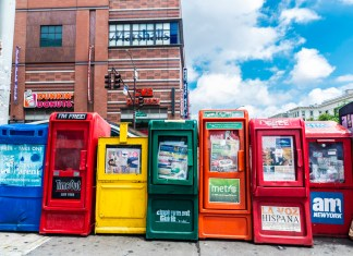 photograph of newspaper vending machines with businesses in background