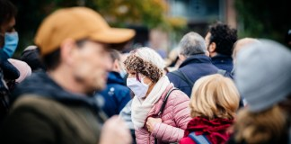 photograph of masked and unmasked people in a crowd