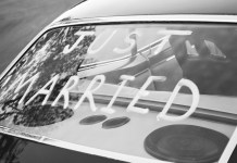"black and white photograph of ""Just Married"" in back window of vintage car"