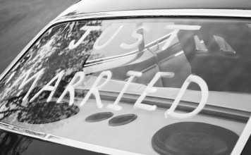 """black and white photograph of """"Just Married"""" in back window of vintage car"""