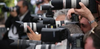 photograph of crowd of paparazzi cameras at event