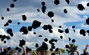 photograph of graduation caps thrown in the air