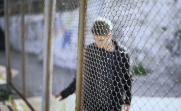 photograph of teen boy confined behind chain link fence