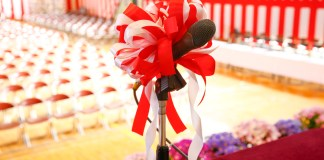 photograph of mic on graduation stage before empty chairs