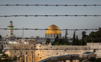 photograph of Jerusalem through barbed wire fence