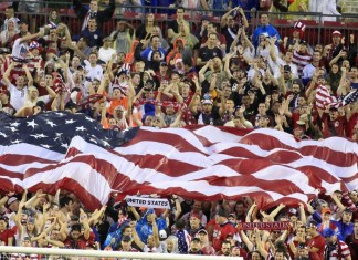 photograph of fans in crowded stadium holding one big American flag
