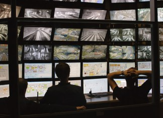 photograph of silhouettes watching surveillance monitors