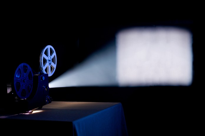photograph of old movie projector displaying blank image on screen