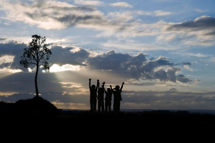 photograph of four silhouetted youths at sunset