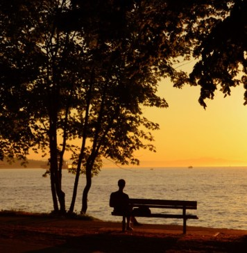 photograph of silhouetted figure alone on bench at sunset