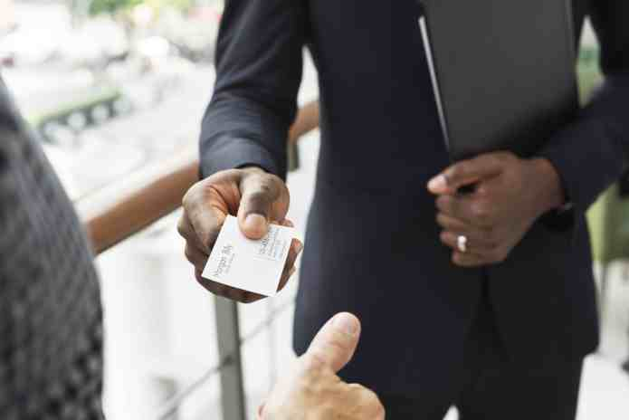 A person giving their business card to a prospective customer