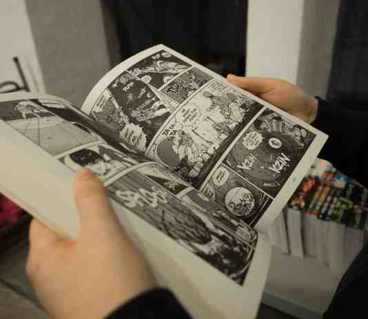 Man holding a black and white comic book
