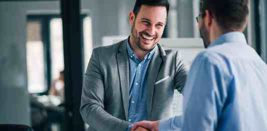 Portrait of cheerful young manager handshake with new client