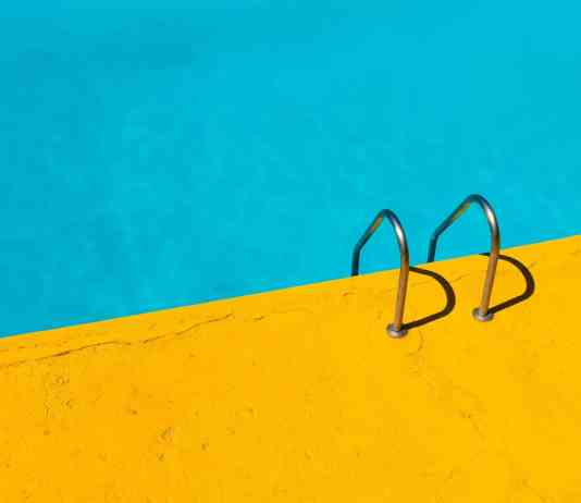 A picture of a pool and ground with the color combination of blue and yellow
