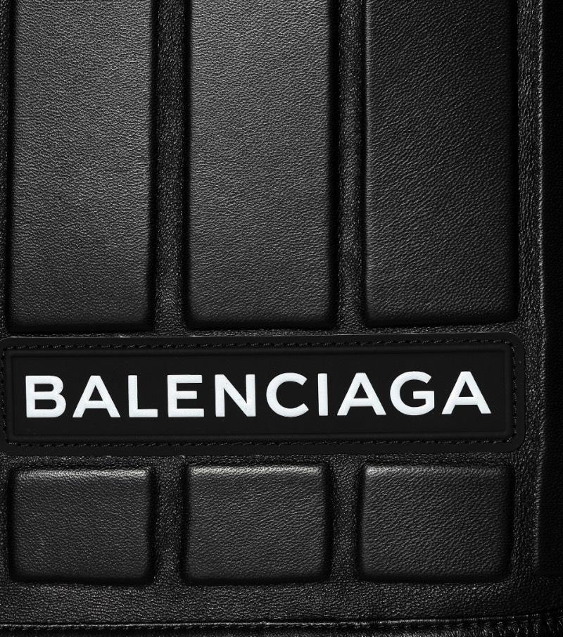 De acordo com o site da Balenciaga, essa saia de couro apareceu para o mundo no Paris Fashion Week e ela transforma o funcional em formal com estilo. Tudo isso porque ela apresenta um padrão interessante feito de couro preto e que é reforçado por neoprene, por uma estética mais utilitária. Além de todo esse visual, essa saia de couro faz parte de uma série chamada logomarca, onde o nome da marca aparece de forma assimétrica e bem proeminente. Mas, o que que foi isso tudo que eu li aqui?
