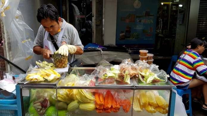 sprzedawca owoców w Bangkoku kroi ananasa