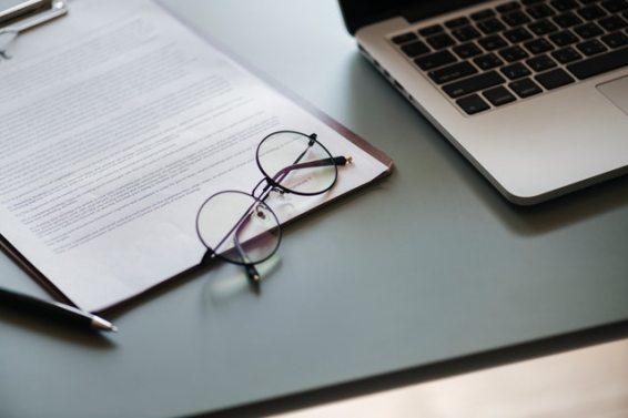 dokument z okularami koło laptopa