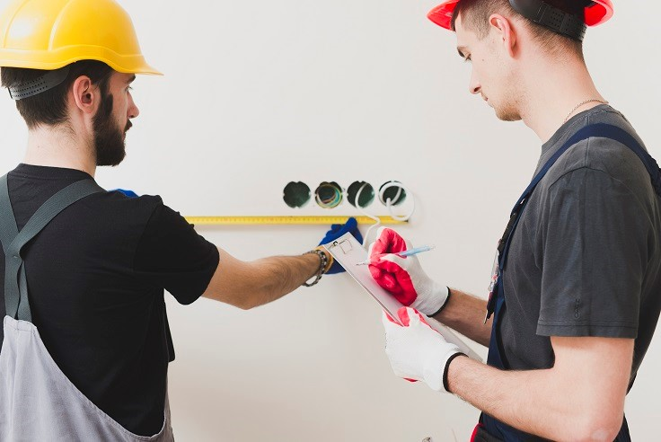 Two workers checking electrical safety