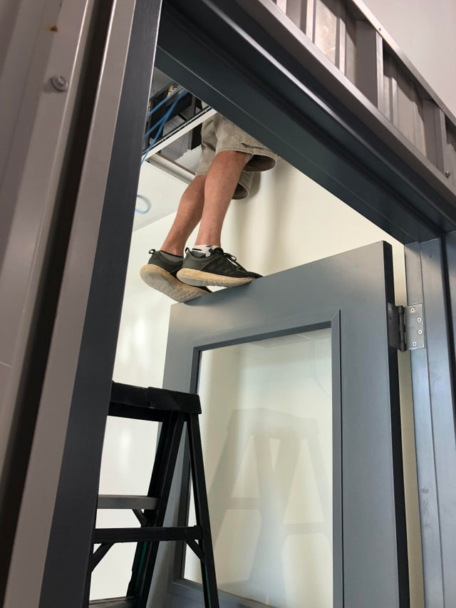 OSHA fail: A man balancing on a door frame to get into the ceiling space.