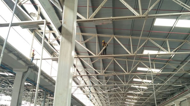 OSHA fails: two men on scaffolding with no harnesses.