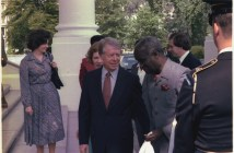 Jimmy Carter and Kenneth Kaunda are talking and appear to be walking into a building. Other people follow behind the presidents.