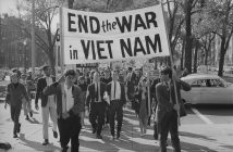 "A black and white photograph shows a group of young people walking together behind a large banner with the text ""End the War in Viet Nam."""