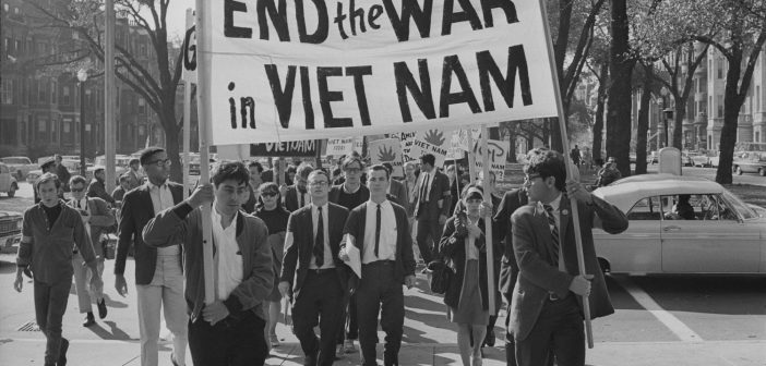 """A black and white photograph shows a group of young people walking together behind a large banner with the text """"End the War in Viet Nam."""""""