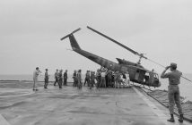 A black and white photograph displays a group of soldiers pushing a helicopter off a landing area into the sea.