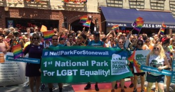 "A photograph shows a group of people standing in front of the Stonewall Inn. At the front of the group, several people hold a banner that reads ""1st National Park for LGBT Equality"" and includes the NCPA logo."