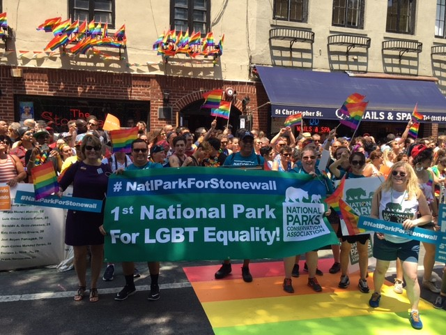 """A photograph shows a group of people standing in front of the Stonewall Inn. At the front of the group, several people hold a banner that reads """"1st National Park for LGBT Equality"""" and includes the NCPA logo."""