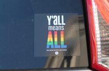 "An image shows a sticker in the back of the car with the text ""Y'all means all."" The word ""all"" appears in rainbow colors."