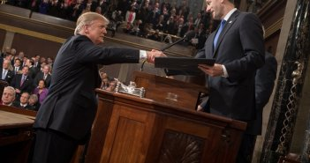 An image shows Paul Ryan standing behind a podium, reaching across the podium to shake hands with Donald Trump.
