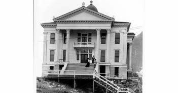A photograph shows a large building with a columned entrance.