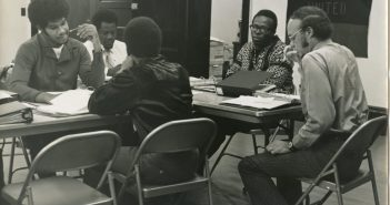"""A black and white photograph shows several men sitting around a table working on papers on the table. A banner in the back reads """"Boston Black United."""""""
