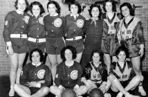 A group of women appear with one row of standing women and one row of seated women. They wear matching uniforms and two basketballs appear on the ground in front of the seated women.